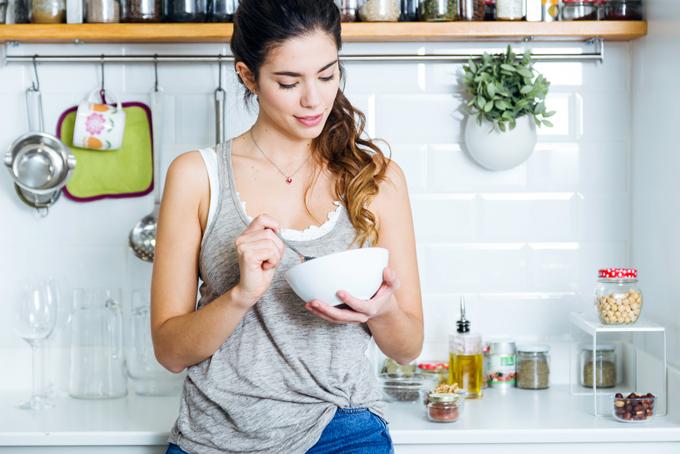 白い器を持って食事している女性の画像