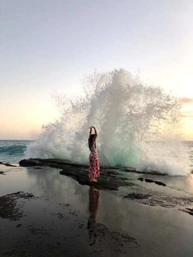ハワイの海、波しぶきぎわでアンジェラさんが手を上げている