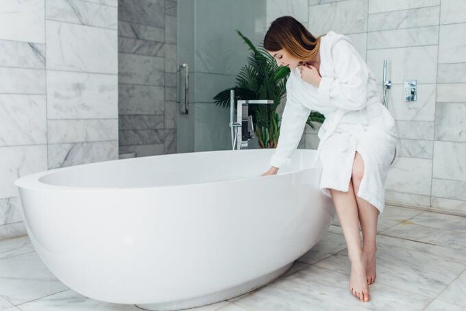 浴槽に手を入れてお風呂の温度を確認している女性のイメージ画像