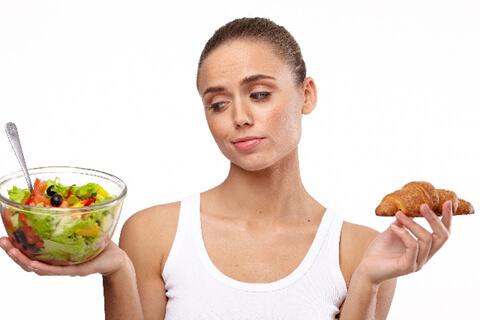 サラダとパンを持ち、悩む女性