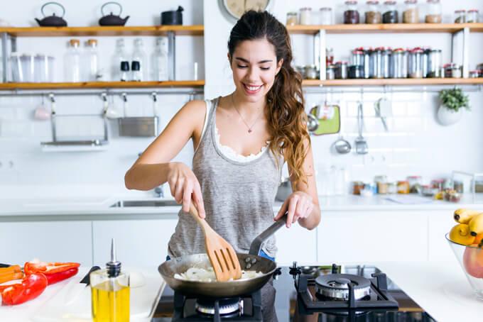 フライパンで調理している女性の画像