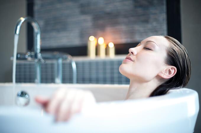 お風呂に入って目をつぶっている女性の画像