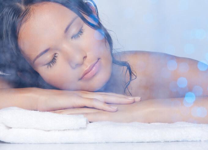 タオルの上に手をおいてその上に顔を乗せている女性の画像