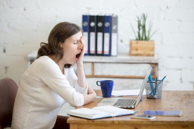 眠そうにあくびをする女性