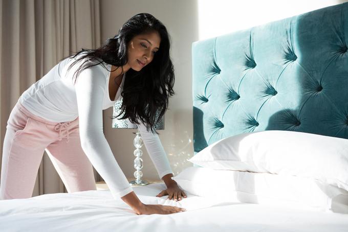 ベッドのシーツを伸ばしている女性