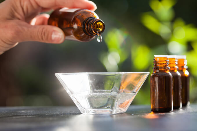 アロマ精油のを水に入ったグラスに垂らしている画像