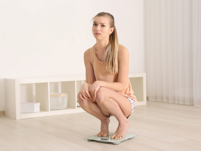 体重計に乗り浮かない表情の女性