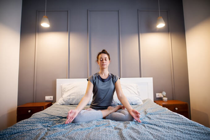 ベッドの上で呼吸法を行っている女性