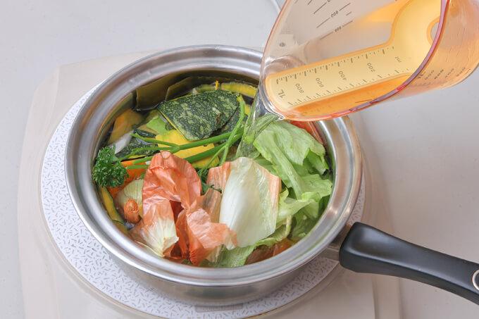 野菜くずを鍋に入れて水を足している画像