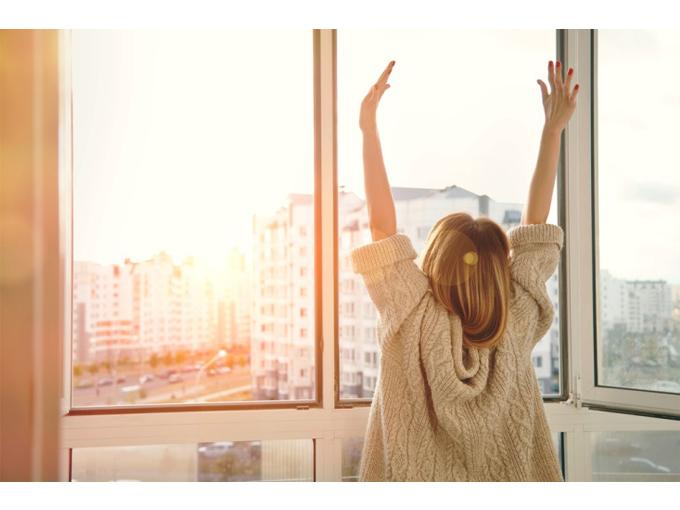 朝起きて伸びをしている女性