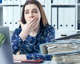 仕事中に眠そうにしている女性