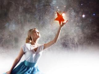 星を見つめて手にする女性の画像