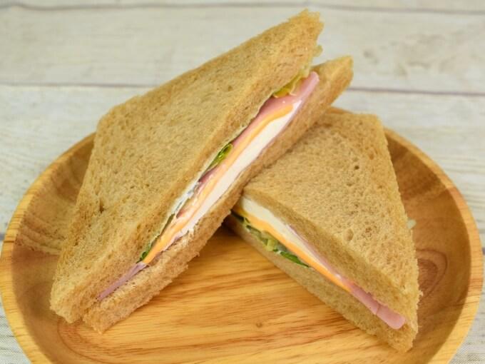 お皿に盛った「全粒粉サンド2種チーズとハム」の画像
