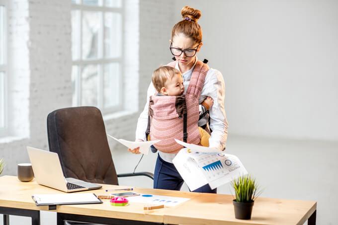 赤ちゃんを抱きながら仕事の資料を見ている女性