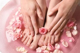 花びらの散ったお湯で足湯をしている女性の足