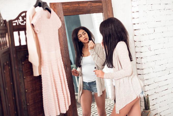 鏡を見ながらメイクをしているショートパンツを履いた女性