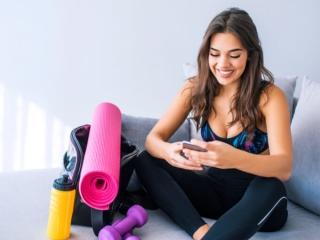 スマートフォンを見るトレーニング女子の写真