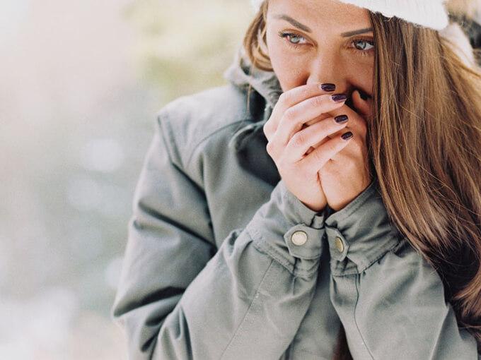 手を温めている女性の画像