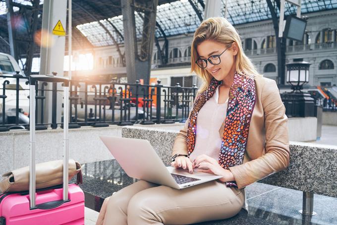 旅先でパソコンを開いている女性の画像