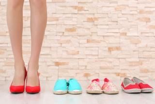 靴が並んだそばで赤いパンプスを履いている女性の足もと