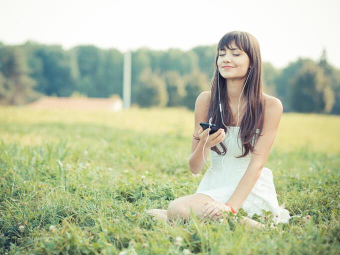 スマートフォンで音楽を聴いている女性の画像