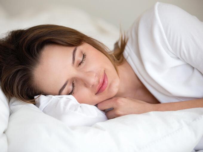 気持ちよさそうに眠る女性の画像