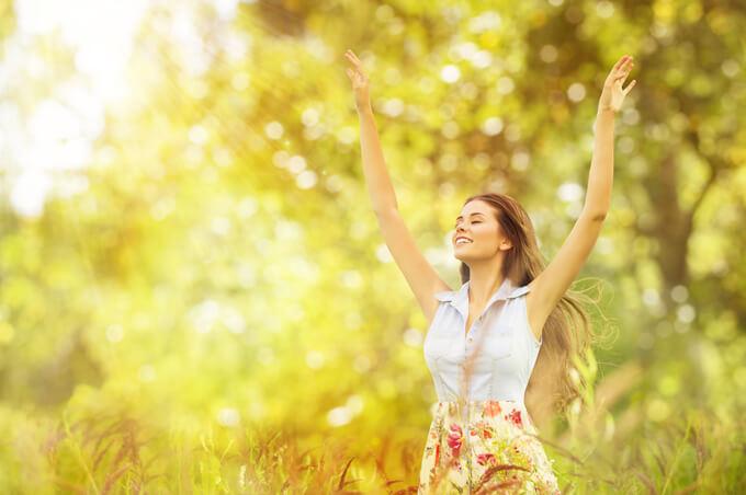 自然の中で気持ち良く両腕を上げている女性