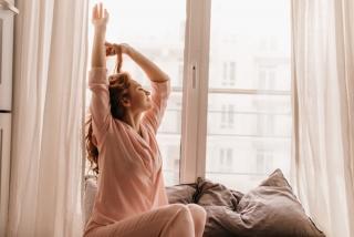 寝起き、伸びをしている女性の画像