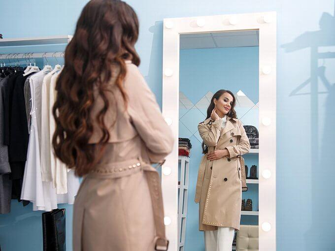 スプリングコートを着て鏡の前に立つ女性