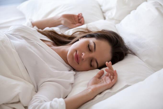 腕を広げて寝ている女性の画像
