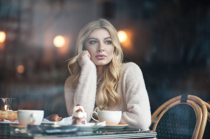 カフェでぼーっと外を見ている女性の画像