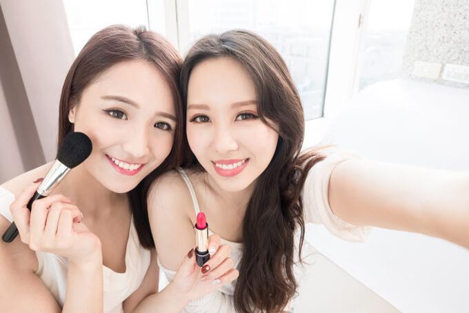 口紅とブラシを持って自撮りしている女性2人