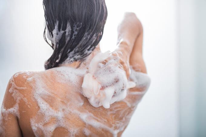 バスルームで背中を洗っている女性の画像