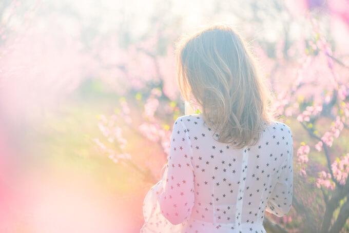 桃の花の木のそばにいる女性の後ろ姿