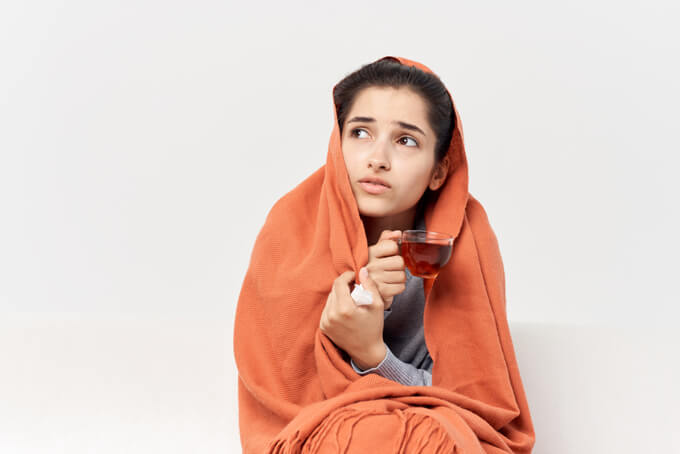 寒そうにしている女性の画像