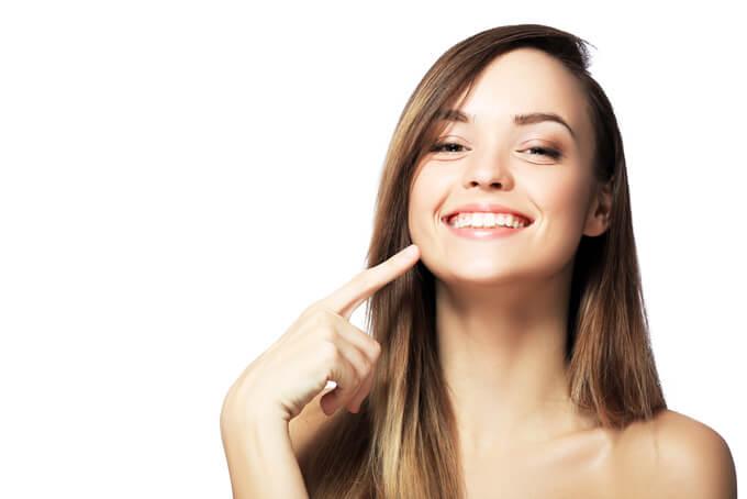 笑顔で口角に手を当てている女性の画像