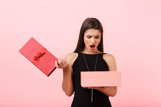 箱の中を見てがっかりしている女性