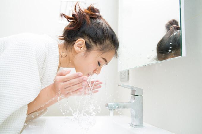 洗面所で顔を洗う女性の画像
