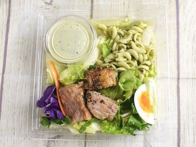 容器のふたを外した「グリルチキンのサラダクリーミーバジルソース付」の画像