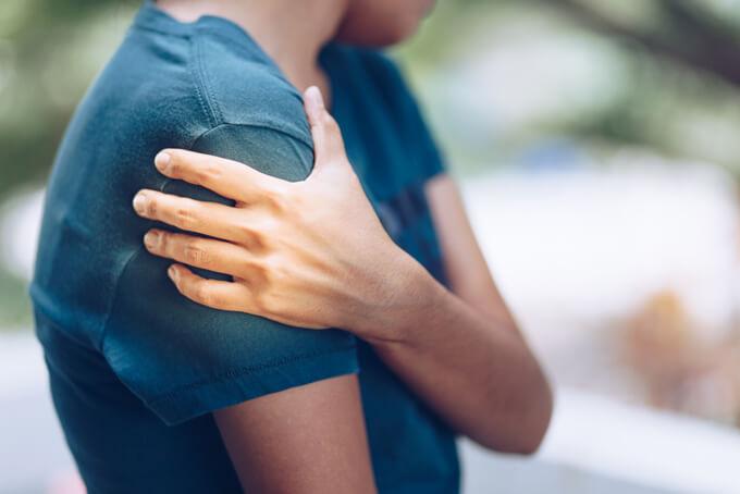 自分の二の腕を触る女性の画像