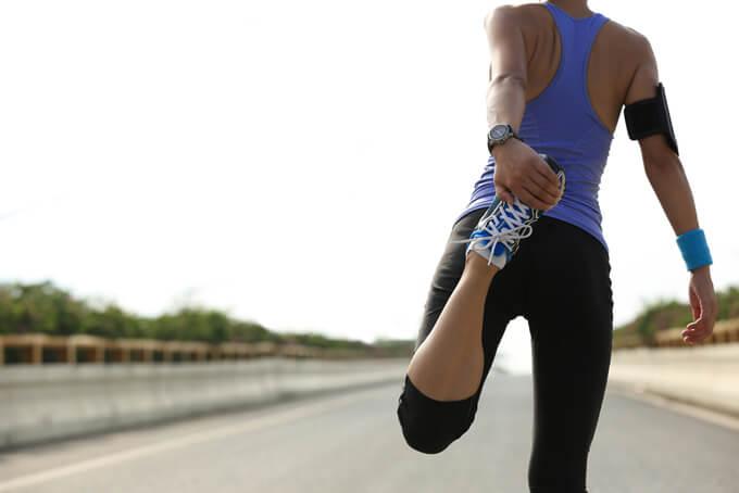 ランニング中足をストレッチしている女性の画像