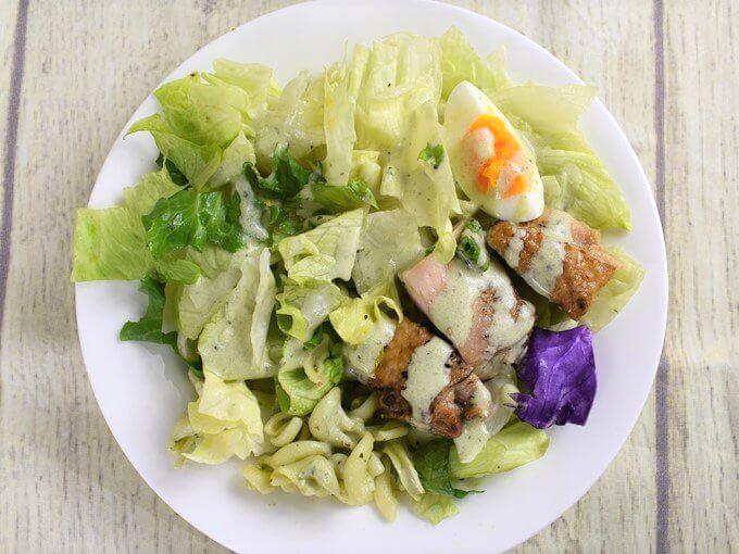 皿に盛りつけた「グリルチキンのサラダクリーミーバジルソース付」の画像