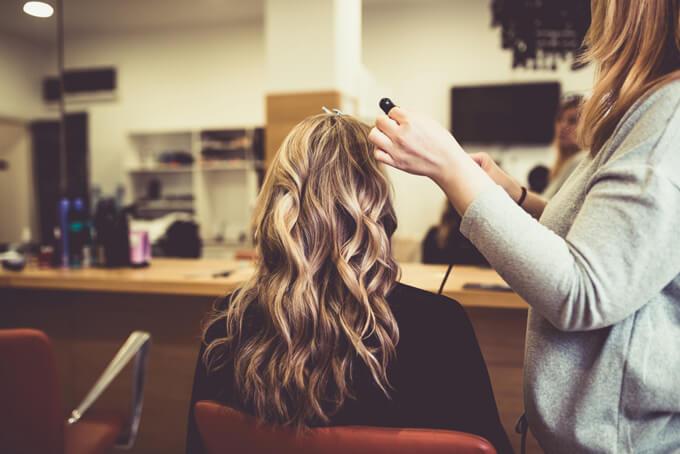 美容室で巻き髪にしてもらっている女性