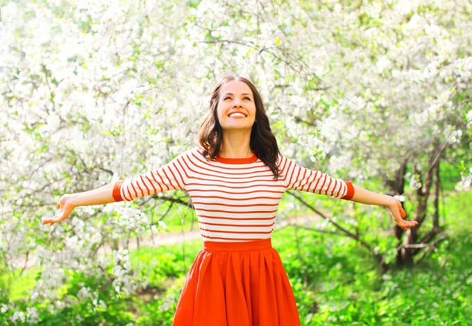 花畑で手をひろげる女性