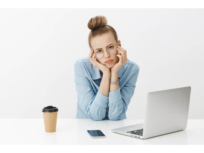 パソコンの前でメガネをかけた女性が悩んでいる