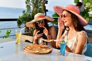 テラスでピザを食べている女性2人