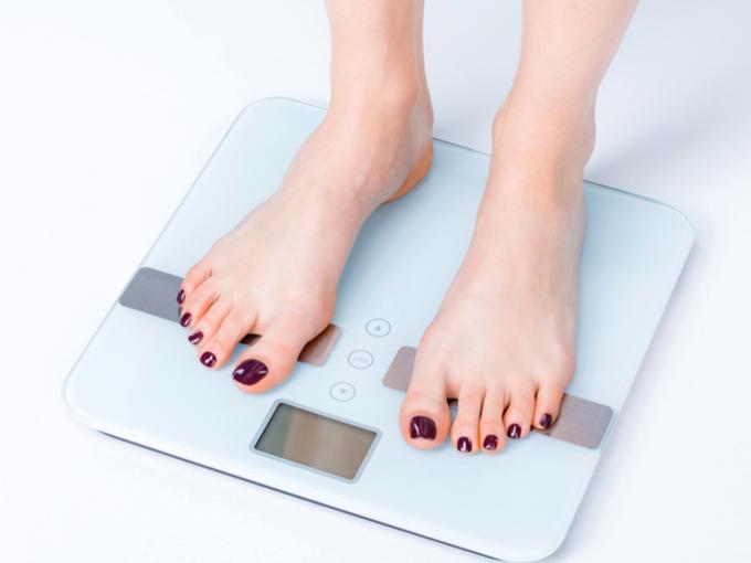 女性が体重計にのっている画像