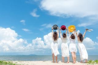 広い海に向かって女性4人が帽子を上にあげている後ろ姿