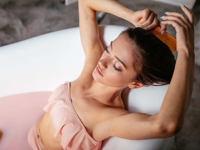 自分の髪をとかす女性の画像