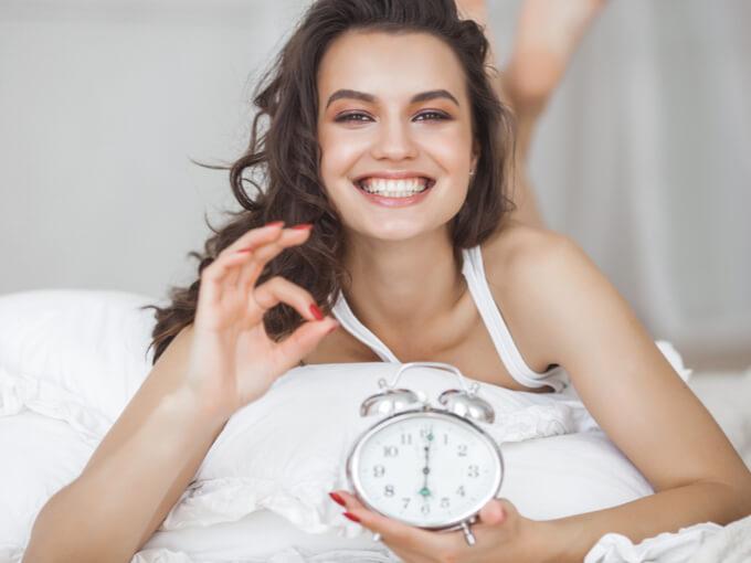 目覚ましを止めようとしている女性の画像